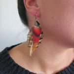 boucle-d'oreille-plume-naturelle-rouge-visage